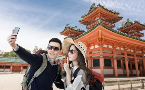 A young and fashionable Asian couple taking a selfie in front of the Heian Shrine, Kyoto, Japan.